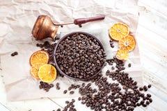 Chicchi di caffè ed il Turco per caffè su una tavola di legno immagini stock libere da diritti