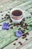 Chicchi di caffè, fiore porpora e caffè della tazza su vecchio fondo verde rustico Fotografia Stock Libera da Diritti