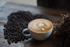 Chicchi di caffè a forma di come un cuore con i fiori secchi Fotografia Stock