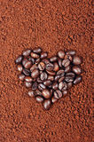 CHICCHI DI CAFFÈ A FORMA DI DEL CUORE SUL FONDO DEL CAFFÈ ISTANTANEO Immagini Stock