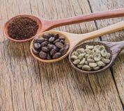 Chicchi di caffè freschi, caffè arrostito, caffè macinato, cucchiaio di legno Fotografia Stock
