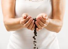 Chicchi di caffè in mani delle donne Immagine Stock Libera da Diritti
