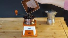 Chicchi di caffè messi nel macinacaffè manuale archivi video