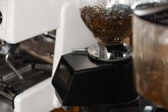 Chicchi di caffè nel saltatore della smerigliatrice, primo piano fotografie stock libere da diritti