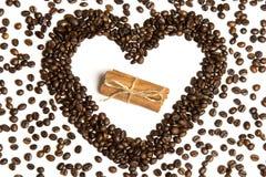 Chicchi di caffè nella forma del cuore e cannella nel centro Fotografia Stock