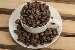 Chicchi di caffè nella tazza e sul piattino Immagini Stock
