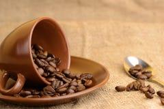 Chicchi di caffè nella tazza marrone e nel cucchiaio Fotografia Stock Libera da Diritti