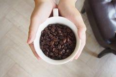 Chicchi di caffè nella tazza sulla vista superiore delle mani Fotografie Stock Libere da Diritti