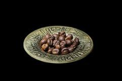 Chicchi di caffè in piatto di oro Fotografia Stock