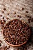 Chicchi di caffè in piatto sulla borsa Fotografia Stock Libera da Diritti