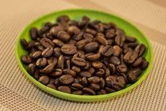 Chicchi di caffè in piatto verde Fotografia Stock Libera da Diritti