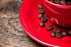 Chicchi di caffè in primo piano rosso della tazza Immagini Stock