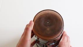 Chicchi di caffè di recente arrostiti, in un barattolo di plastica da un macinacaffè stock footage
