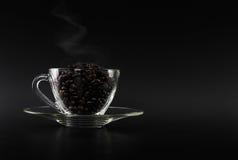 Chicchi di caffè scuri sulla tazza di vetro Fotografie Stock