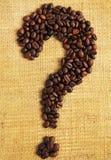 Chicchi di caffè sistemati come punto interrogativo su fondo strutturato Fotografie Stock