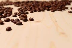 Chicchi di caffè sparsi sulla tavola Immagine Stock