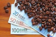 Chicchi di caffè su euro soldi Immagine Stock