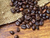 Chicchi di caffè su insaccamento con il fondo di legno, primo piano estremo fotografia stock