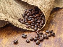 Chicchi di caffè su insaccamento con il fondo di legno, primo piano estremo immagine stock libera da diritti