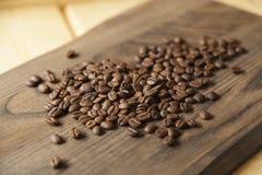 Chicchi di caffè su priorità bassa di legno fotografie stock