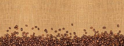 Chicchi di caffè su struttura naturale della tela da imballaggio fotografie stock