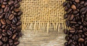 Chicchi di caffè su tela da imballaggio e su legno Fotografia Stock