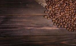 Chicchi di caffè su un bordo di legno Immagine Stock
