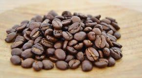 Chicchi di caffè su un bordo di legno Immagini Stock