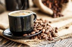 Chicchi di caffè su un bordo di legno e su una tazza di caffè Immagine Stock