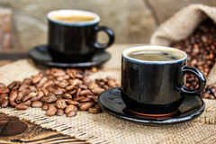 Chicchi di caffè su un bordo di legno e su una tazza di caffè Fotografia Stock