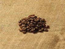 Chicchi di caffè su un fondo della tela di iuta Fotografia Stock