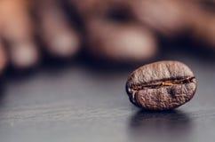 Chicchi di caffè su un fondo nero Chicchi di caffè di levitazione Prodotto granuloso Bevanda calda Fine in su Raccolta Sfondo nat Fotografia Stock