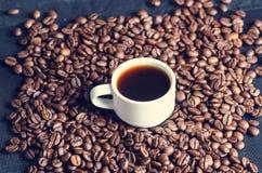 Chicchi di caffè su un fondo nero Chicchi di caffè grezzi Prodotto granuloso Bevanda calda Fine in su Raccolta Sfondo naturale En Fotografie Stock