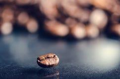Chicchi di caffè su un fondo nero Chicchi di caffè grezzi Prodotto granuloso Bevanda calda Fine in su Raccolta Sfondo naturale En Immagini Stock