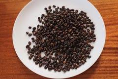 Chicchi di caffè su un piatto fotografia stock libera da diritti