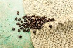 Chicchi di caffè su un sacco della tela da imballaggio e sulle mattonelle blu Fotografia Stock