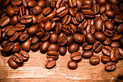 Chicchi di caffè su una vecchia tavola di legno per fondo Spazio per tex Immagine Stock