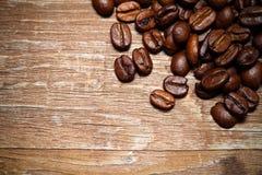 Chicchi di caffè su una vecchia tavola di legno per fondo Spazio per tex Immagini Stock