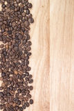 Chicchi di caffè sui precedenti dei bordi di legno Fotografia Stock