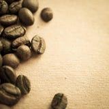 Chicchi di caffè sul fondo d'annata della carta di colore fotografie stock