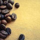 Chicchi di caffè sul fondo d'annata della carta di colore fotografia stock libera da diritti