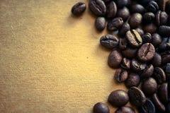 Chicchi di caffè sul fondo d'annata della carta di colore immagini stock