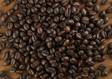 Chicchi di caffè sul fondo di legno della tavola Fotografia Stock Libera da Diritti