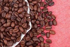 Chicchi di caffè sul fondo rosso del panno Fotografie Stock Libere da Diritti