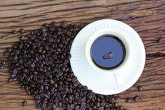 Chicchi di caffè sul pavimento di legno Immagine Stock
