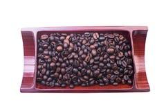 Chicchi di caffè sul piatto isolato su bianco Fotografie Stock