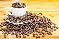 Chicchi di caffè sulla tazza e sulla tavola di legno Fotografie Stock Libere da Diritti