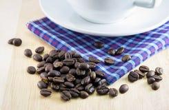 Chicchi di caffè sullo scrittorio di legno con la tazza di caffè Fotografie Stock Libere da Diritti