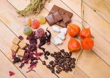 Chicchi di caffè, tè dell'ibisco, zucchero di grumo, cioccolato e marmellata d'arance Immagini Stock Libere da Diritti