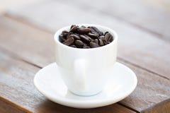 Chicchi di caffè in tazza di caffè Fotografia Stock